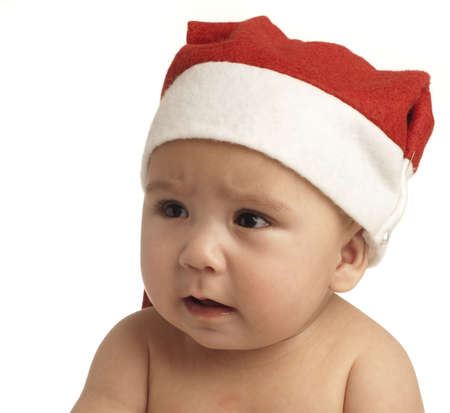 baby crying with christmas hat on white background photo