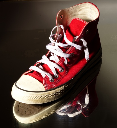 vintage red sneakers on a reflecting surface photo