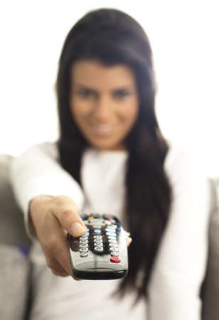 young girl watching tv using a remote control photo