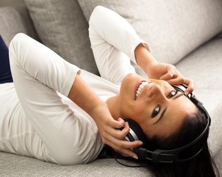 mobile headsets: joven escucha m�sica en un sof�