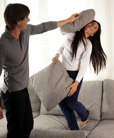 couple fight: boyfriends fighting with pillows on the sofa