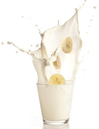 fruit shake: banana slices falling to a milk glass Stock Photo