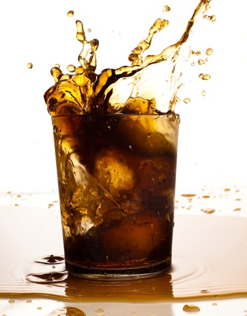 brown refreshment splashing on glass on  white photo