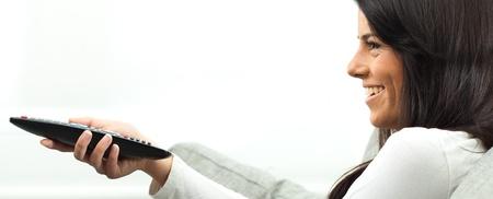 felice ragazza carina con telecomando, guardare la tv
