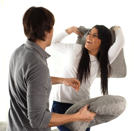 couple fighting with pillows on white background photo