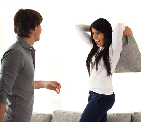 couple fighting with pillows on white background Stock Photo - 8849696