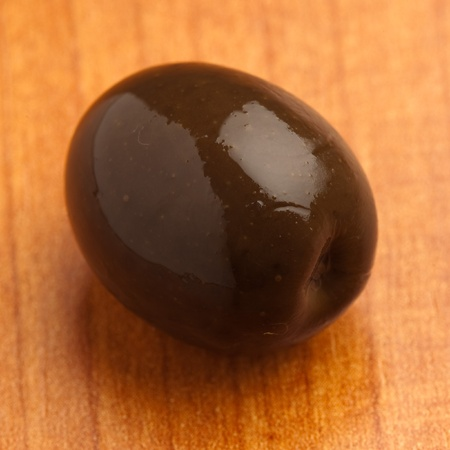single black olive on a wooden surface photo