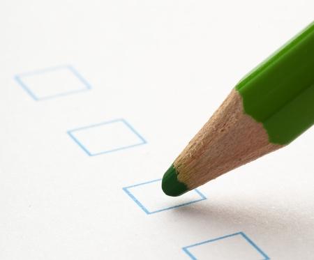test check boxes and green crayons closeup photo
