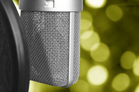 closeup of vintage microphone against abstract yellow lights photo