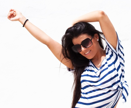 pretty young girl wearing a striped t-shirt and sunglasses, outdoor shot photo
