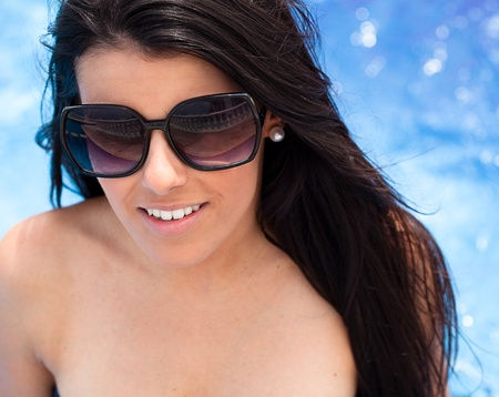 pretty young woman with sunglasses possing against a pool  photo