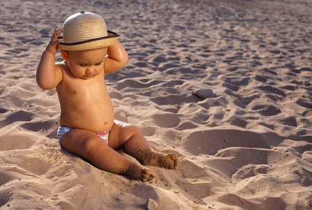 kids playing beach: baby sitting on the sand of the beach with a straw hat at sunset