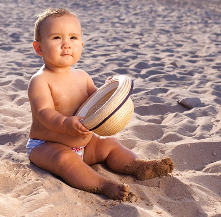 baby sitting on the sand of the beach with a straw hat at sunset photo