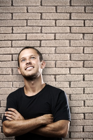 young man smiling against a bricks wall photo