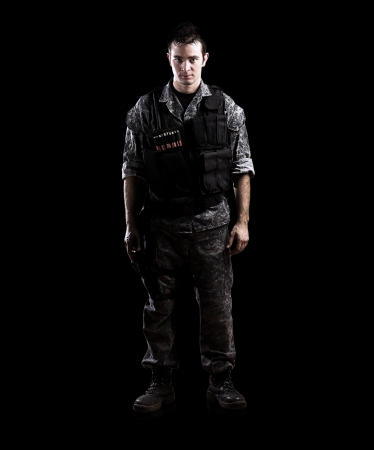combat boots: armed soldier isolated on a black background