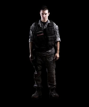 soldado armado aislado en un fondo negro Foto de archivo