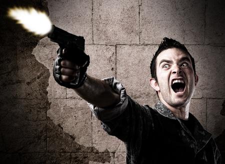 tiro al blanco: hombre disparando una pistola contra una pared erosionada