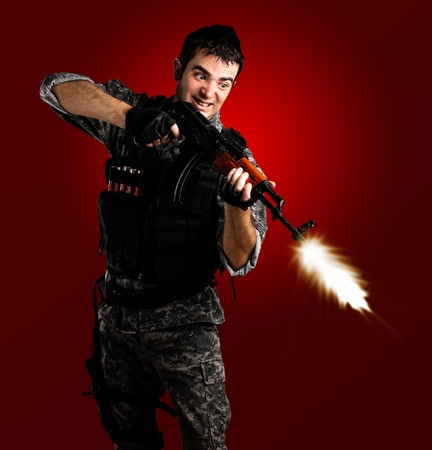 young soldier wearing urban camouflage shooting with a rifle on red background photo