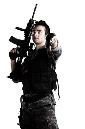 young armed soldier with finger down on white background photo