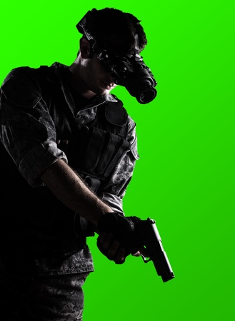 night vision: soldier wearing urban camouflage uniform with night vision goggles armed with a gun on a green background