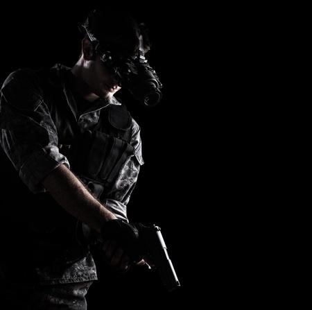 soldaat met stedelijke camouflage-uniform met night vision goggles gewapend met een geweer op een zwarte achtergrond