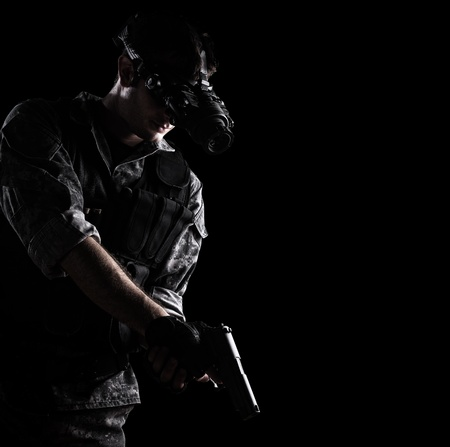 one armed: soldier wearing urban camouflage uniform with night vision goggles armed with a gun on black background