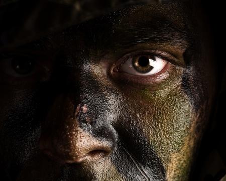 camuflaje: cara de joven soldado con pintura de camuflaje de selva Foto de archivo