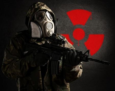 radioattivo: soldato armato indossa una maschera antigas contro un muro di cemento con il simbolo rosso radioattivo