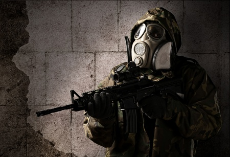 armed forces: armed soldier with gas mask wearing a camouflage uniform against a wall