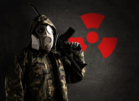 chemical warfare: armed soldier wearing a gas mask against a concrete wall with red radioactive symbol