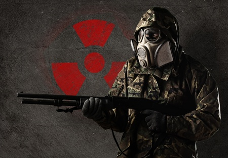 biohazard: armed soldier wearing a gas mask against a concrete wall with red radioactive symbol