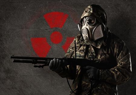 riesgo biologico: soldado armado con una m�scara de gas contra un muro de hormig�n de color rojo con s�mbolo radiactivo