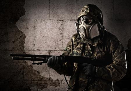 soldado: armado soldado con m�scara de gas, vestido con un uniforme de camuflaje contra una pared