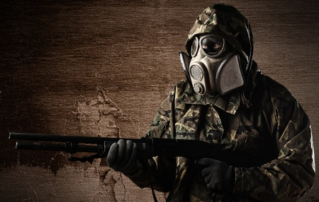 special forces: armed soldier with gas mask wearing a camouflage uniform against a wall
