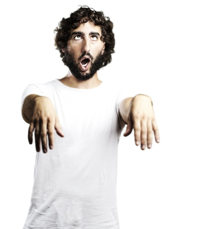 zombie hand: young man imitating a zombie against a white background