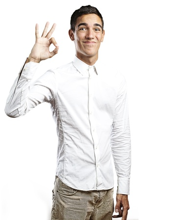 Portrait of a handsome young man smiling and gesturing okay sign against white background Stock Photo - 10384110