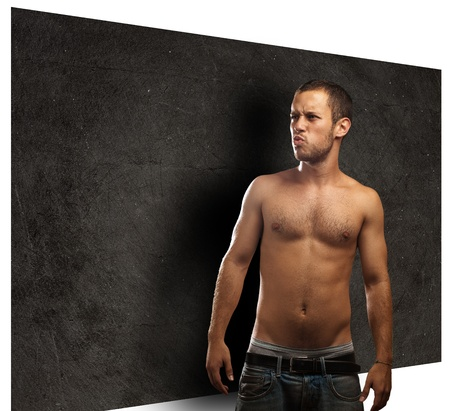 surprised young man against a grunge wall Stock Photo - 10383622