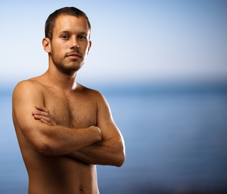 man shirtless with arms crossed in the beach photo
