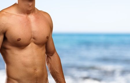 hot boy: strong torso against a sea background
