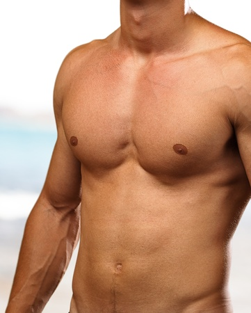 human chest: healthy young man with a beach as a background Stock Photo