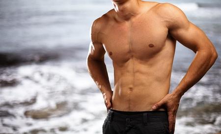 hombre sin camisa: el hombre joven y sano, con una playa como telón de fondo