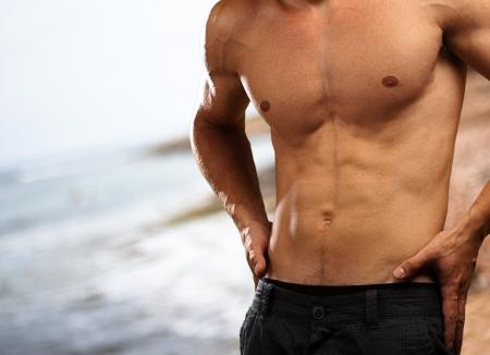 niño sin camisa: el hombre joven y sano, con una playa como telón de fondo