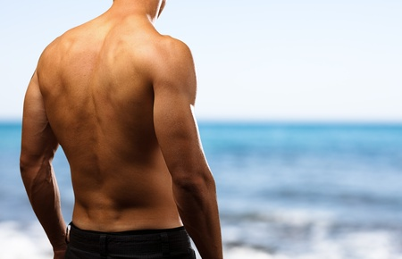 healthy young man with a beach as a background photo