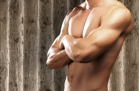 strong torso of young man against a wooden background photo
