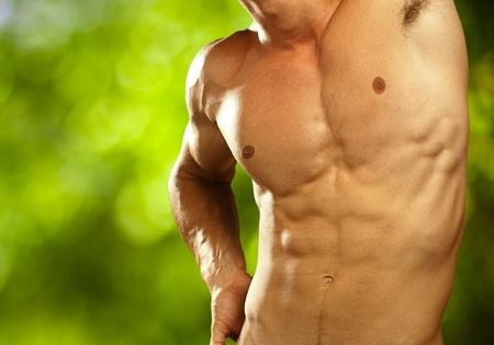 hombre de músculo en un fondo de naturaleza