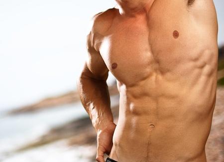 naaktstrand: spier man op een strand achtergrond Stockfoto