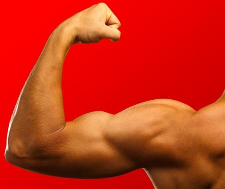 hombre fuerte: b�ceps fuerte sobre un fondo rojo Foto de archivo