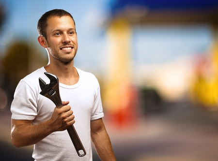 man smiling with a wrench against a oil station Stock Photo - 10384060