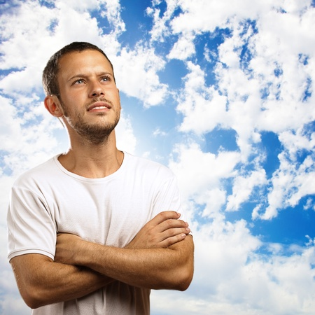 man looking at sky: young man looking up against a sky background Stock Photo