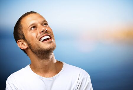 man looking at sky: lucky boy laughing looking up against a beach background Stock Photo